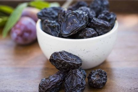 natural condition prunes in white bowl